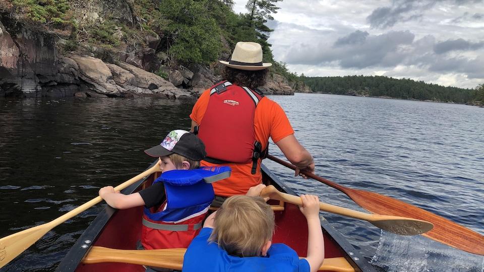 Un adulte et deux enfants dans un canot.
