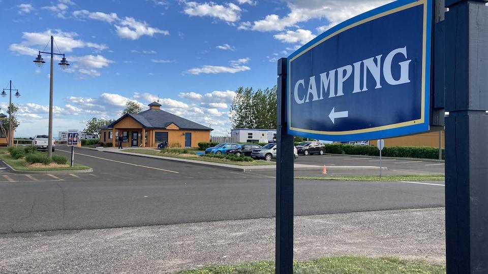 La pancarte indiquant le camping de Carleton-sur-Mer ainsi que le bâtiment d'accueil du site, en arrière-plan.