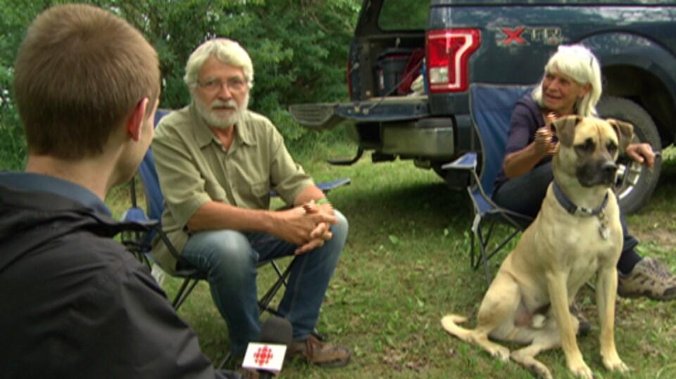 Deux personnes discutent avec un journaliste.