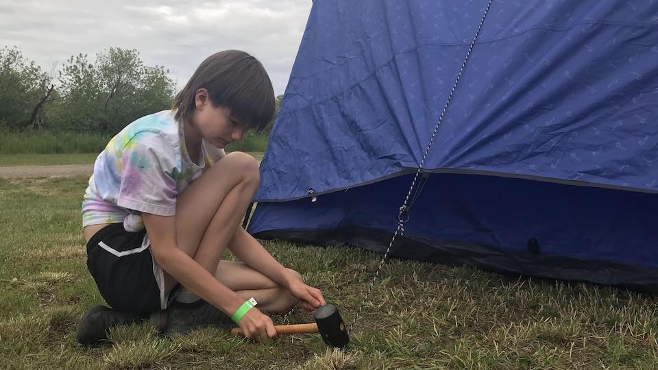 Une jeune fille installe une tente de camping.
