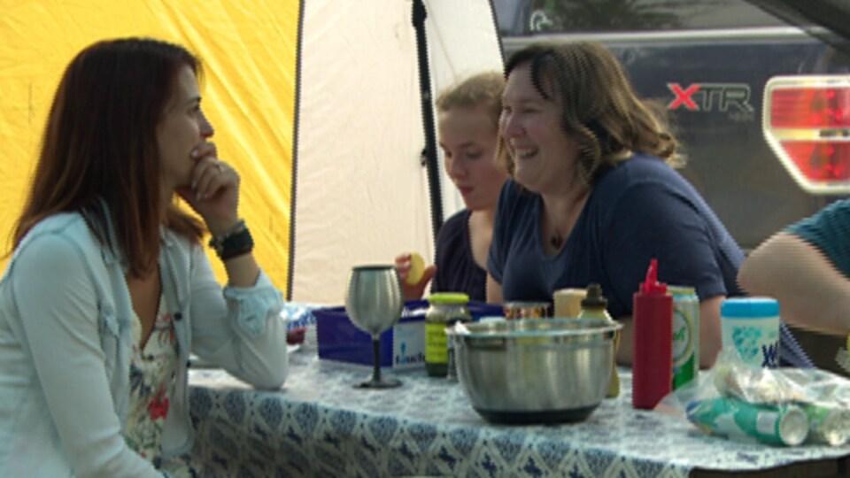 Des femmes discutent autour de la table à l'intérieur d'une tente.