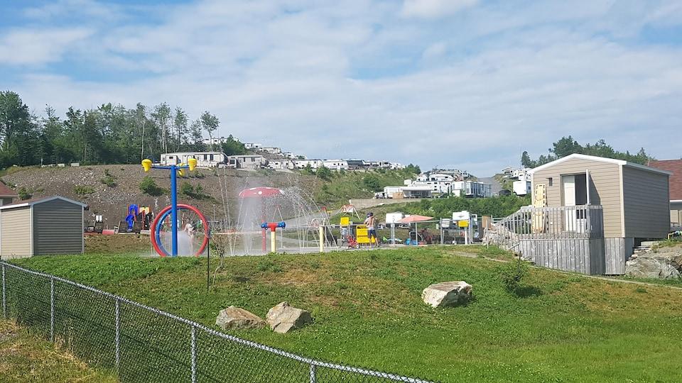 Des enfants et leurs parents s'amusent dans des jeux d'eau devant une colline sur laquelle sont stationnés plusieurs véhicules récréatifs.