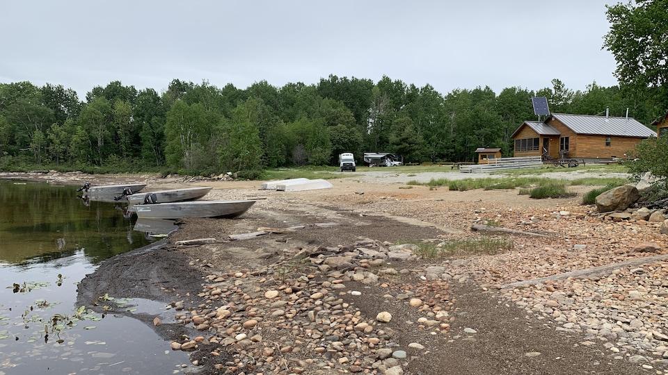 Le niveau du lac Granet est bas à la mi-juin dans la réserve faunique La Vérendrye. Trois embarcations sont placés sur le bord de l'eau près du camping.