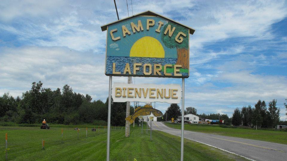 Un soleil, un plan d'eau et un arbre représentent le camping de Laforce sur un panneau.
