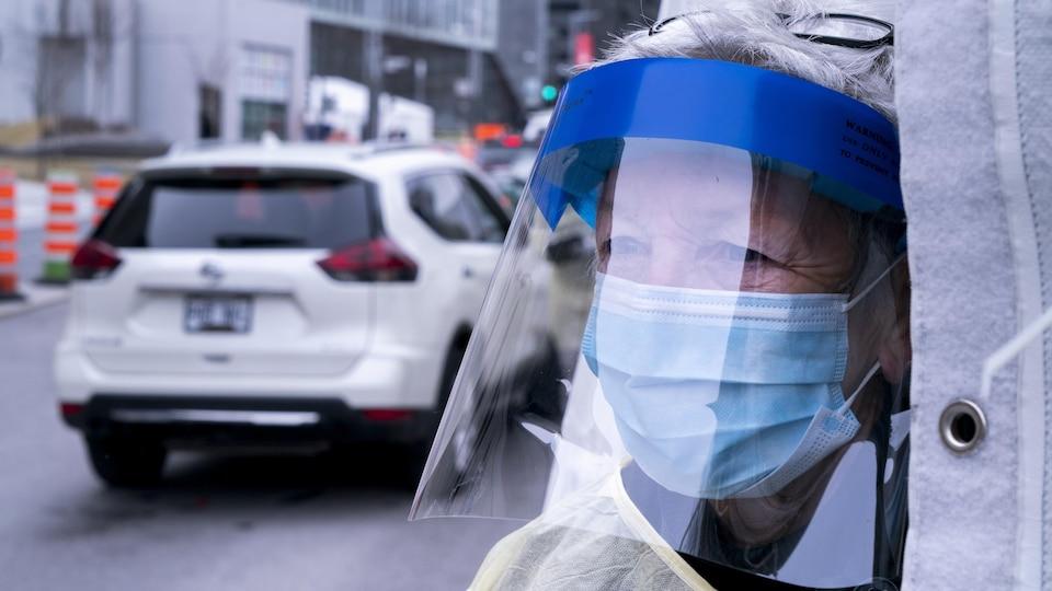 Un travailleur de la santé muni d'un masque et d'une visière.