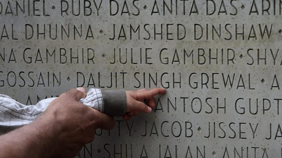 Le doigt d'un bébé qui pointe un mur sur lequel des noms sont gravés.
