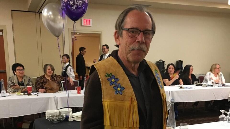 Gros plan sur Alan Rollins, le chef du conseil scolaire Kee Tas Kee Now portant une veste sans manches avec des franges, debout avec en arrière-plan des gens assis autour d'une table.