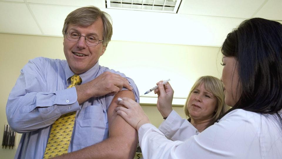 Une infirmière administre un vaccin à un homme dans la soixantaine.