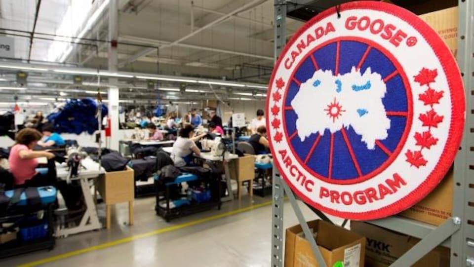 Gros plan sur un logo de Canada Goose, couturières au travail en arrière-plan.