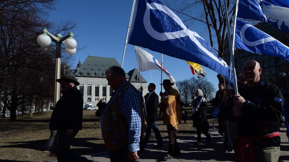 Le président de la Fédération des Métis du Manitoba, David Chartrand (milieu), marche avec le drapeau métis devant la Cour suprême du Canada.