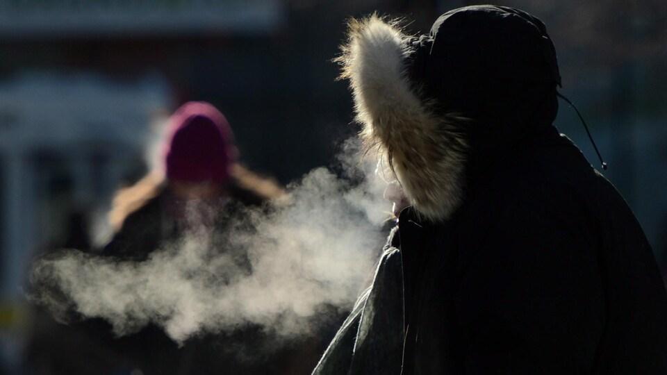 L'haleine d'une personne est blanche dans l'air froid d'hiver.