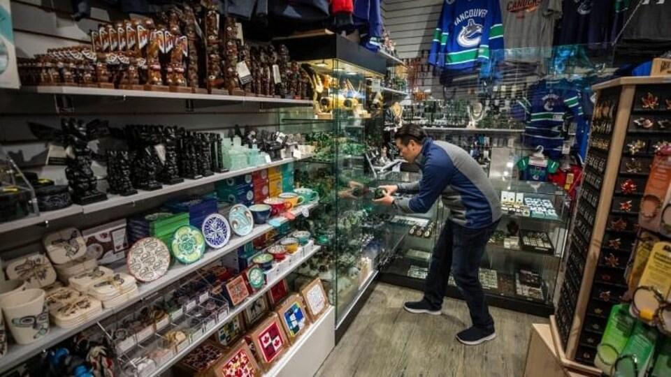 Chris Cheung place de la marchandise sur des étagères du magasin Canadian Crafts, à Vancouver.