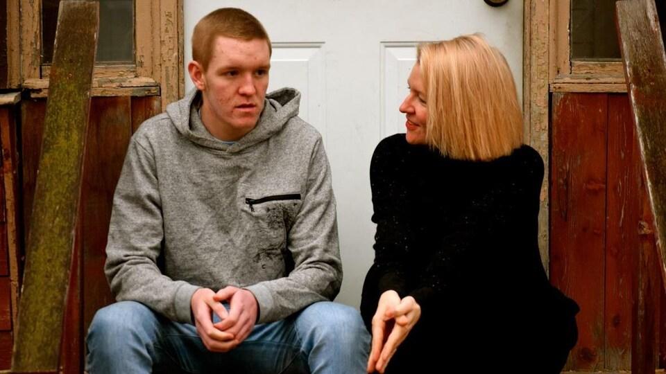 Une femme discute avec un jeune homme, devant une porte.