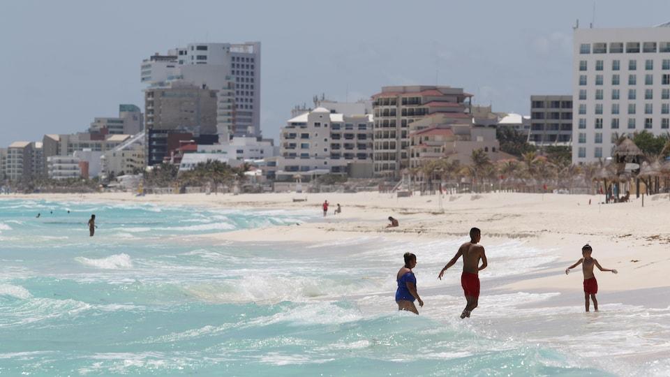 Des gens se baignent dans la mer devant des hôtels.