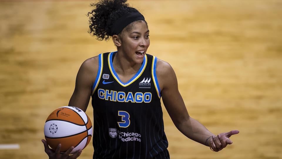 La femme est sur un terrain de basketball, elle tient un ballon d'une main et pointe quelque chose avec son autre main. Elle regarde sur le côté.