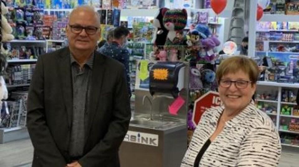 Serge Bergeron et Nicole Bilodeau sourient dans un centre commercial.