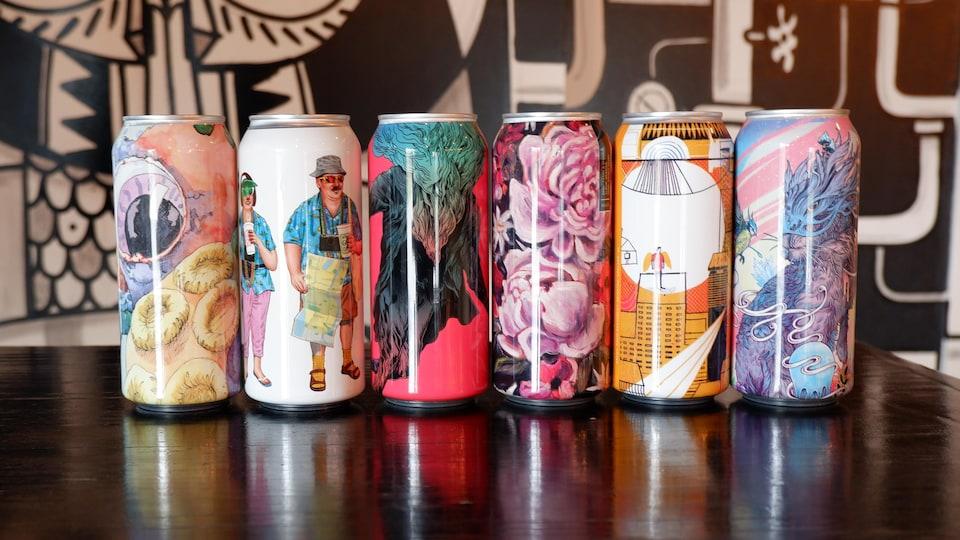 Des canettes de bière de la brasserie Collective Arts sont alignées sur une table.