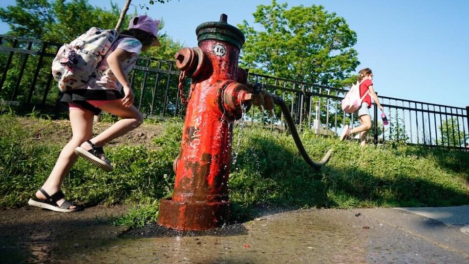 Des enfants marchent près d'une borne-fontaine de laquelle s'écoule de l'eau.
