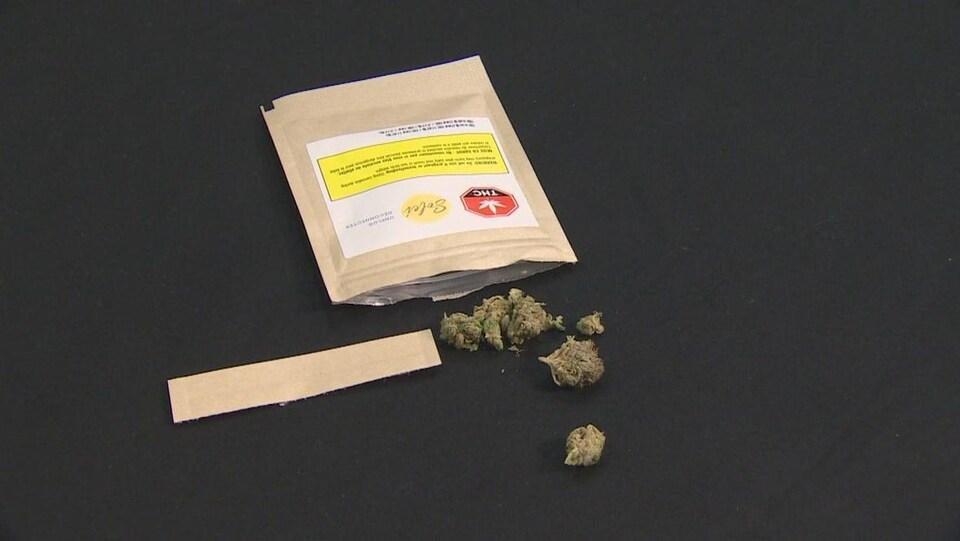 Des fleurs séchées de cannabis s'échappent du sachet couché sur une table