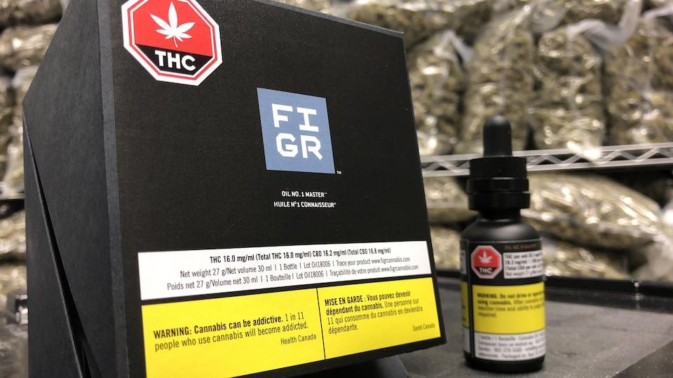 Une petite bouteille d'huile de cannabis à côté de sa boîte en carton, le tout devant un étalage de grands sacs de cannabis séché.