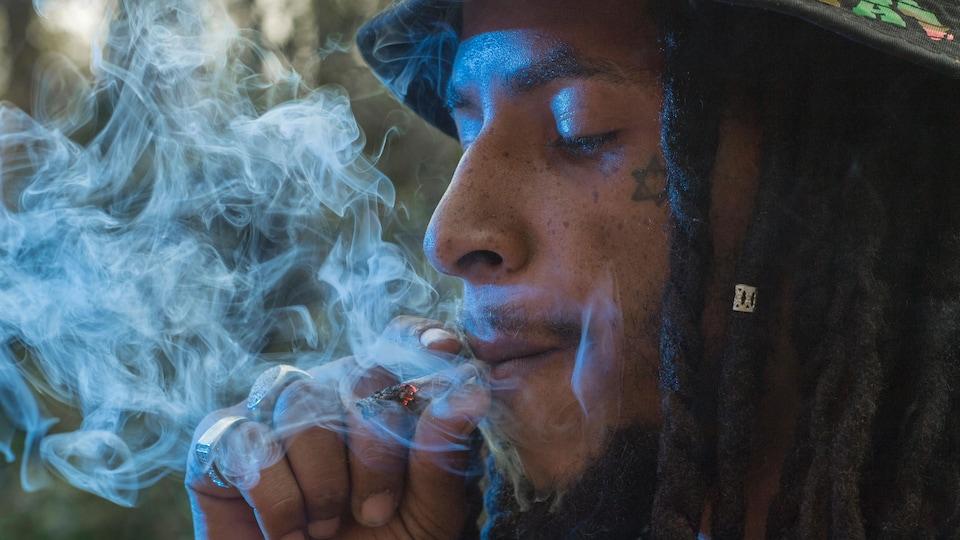Un homme fume du cannabis