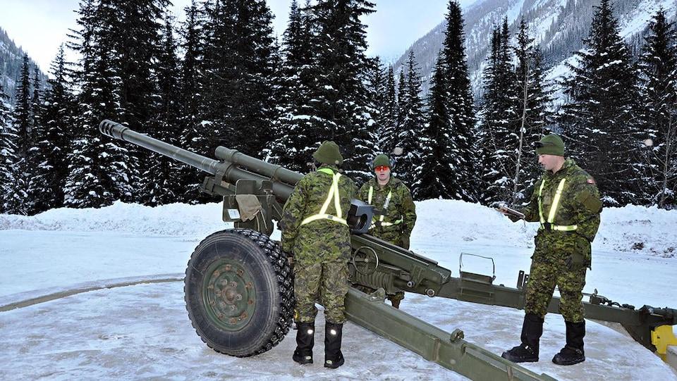 Trois soldats photographiés devant un canon.
