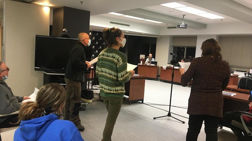 Trois personnes chantent devant les membres du Conseil de ville.