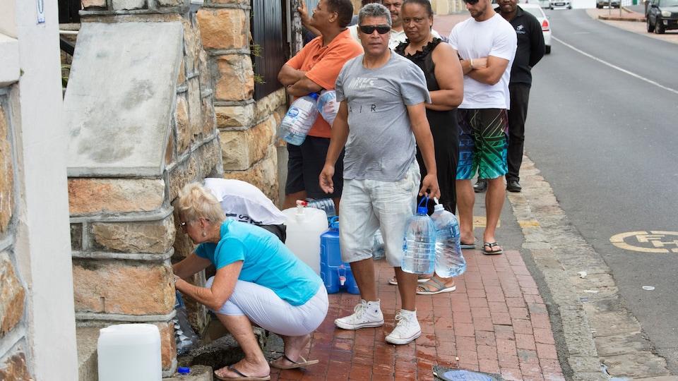 Des citoyens du Cap font la file sur le trottoir avec des bidons de plastique pour s'approvisionner en eau potable à l'aide d'un tuyau relié à une source.