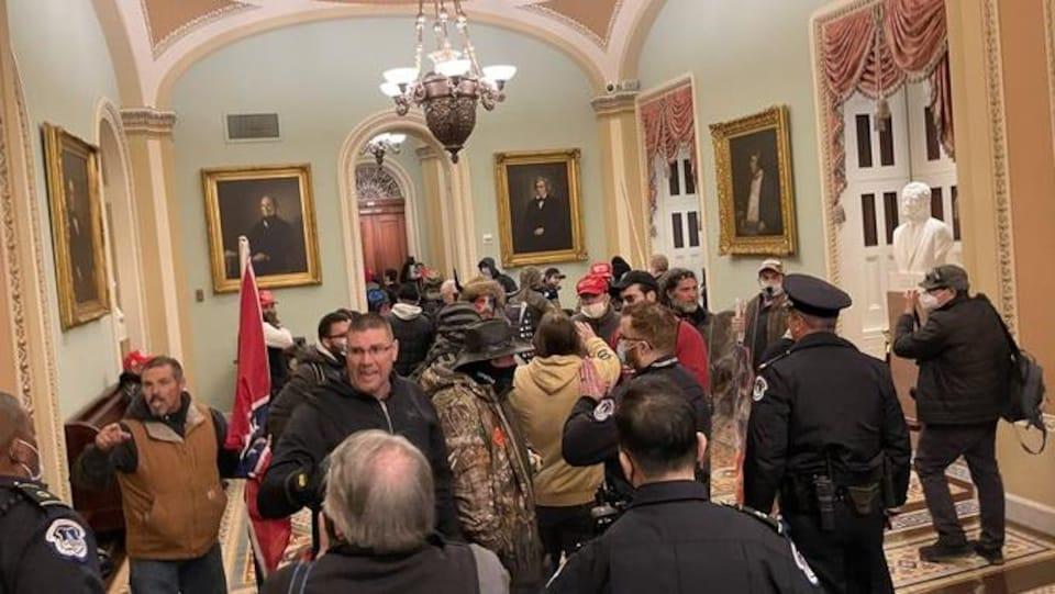 Des policiers se tiennent devant des manifestants dans un couloir du Capitole.