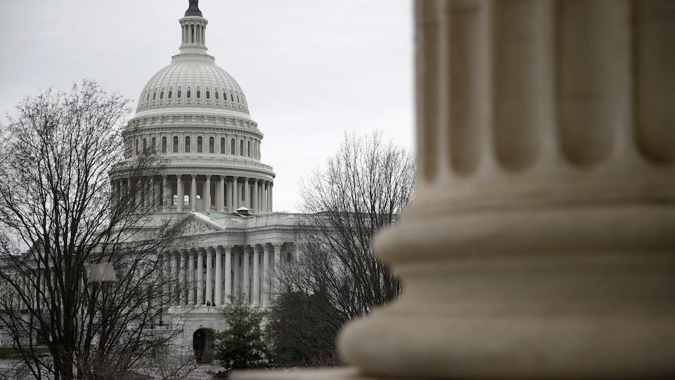 Le Capitole de Washington vu de l'extérieur sous un ciel gris.
