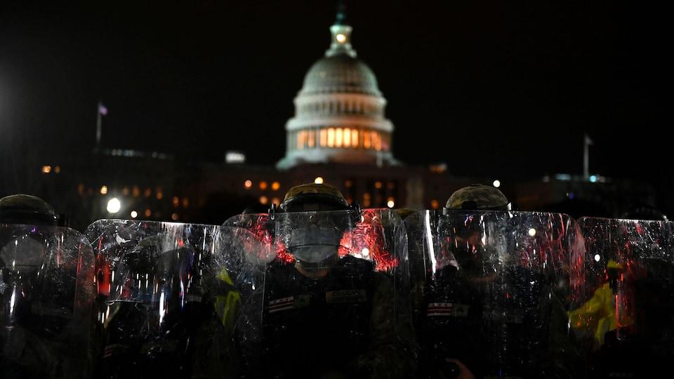 Des policiers et des soldats sont armés de boucliers transparents devant le Capitole.