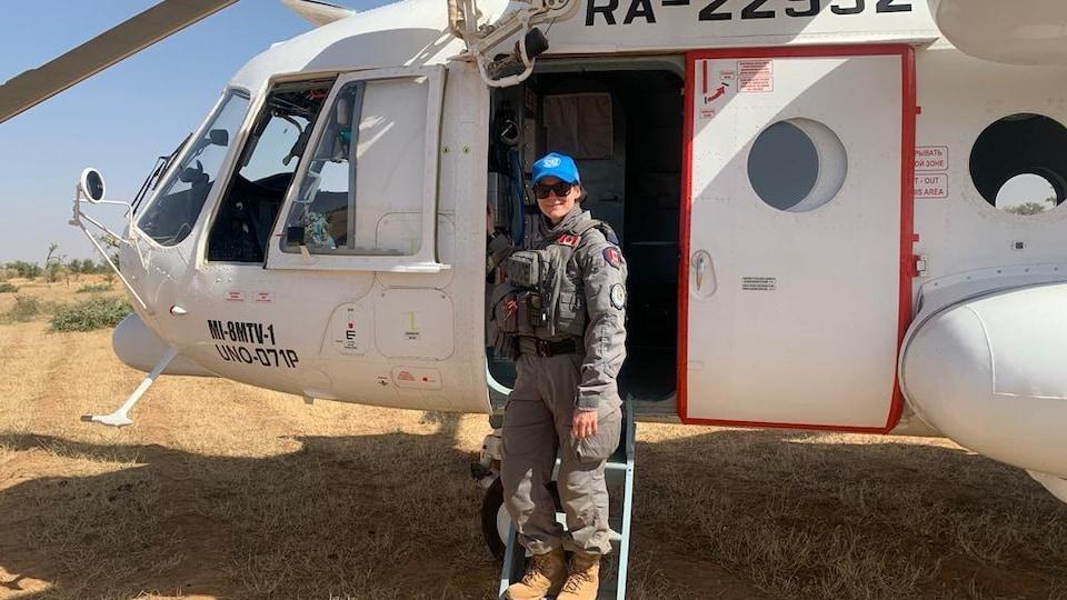 Une militaire est sur les marches d'un hélicoptère