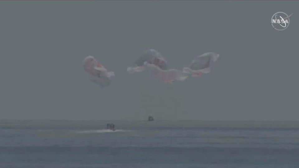 La capsule Crew Dragon à quelques mètres de l'eau, avec ses quatre parachutes déployés.