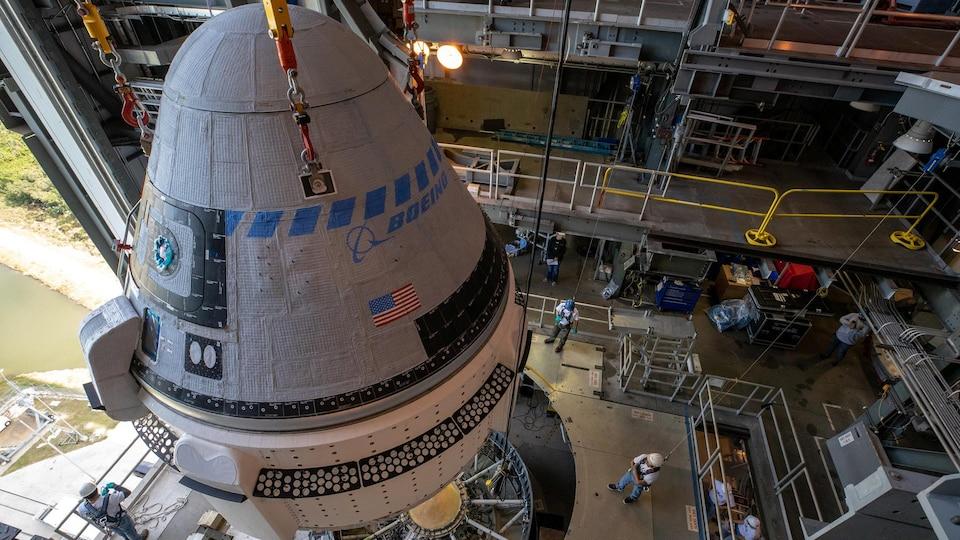 Plan rapproché de la capsule au moment d'être fixée au lanceur.