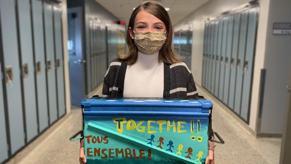 Isabel Feehan tient la capsule temporelle dans ses bras, dans un corridor d'école.