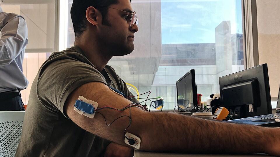 Un détecteur, construit avec de petits fils colorés, est collé sur le bras d'un jeune homme.