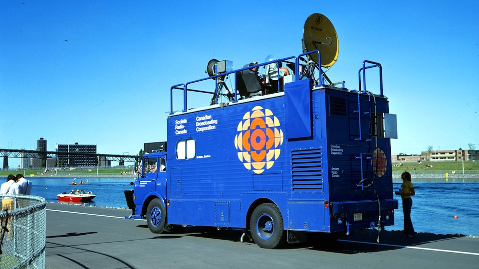 Près du bassin olympique, car de reportage de Radio-Canada avec le logo de la pizza multicolore. Des techniciens sont assis sur le toit du véhicule.