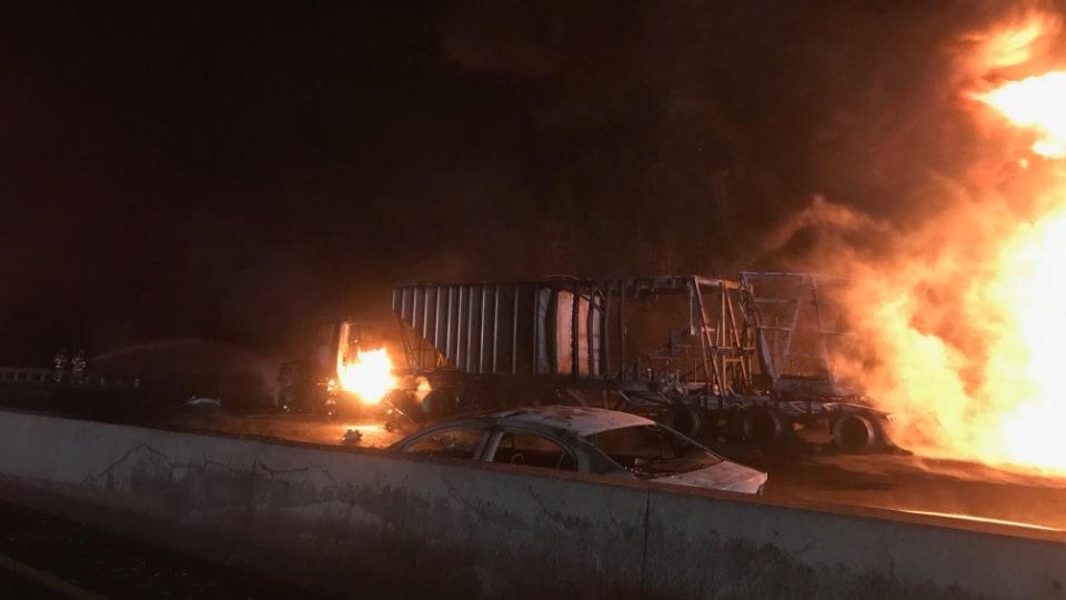Photo de la remorque d'un camion complètement brûlée, alors que le feu fait toujours rage