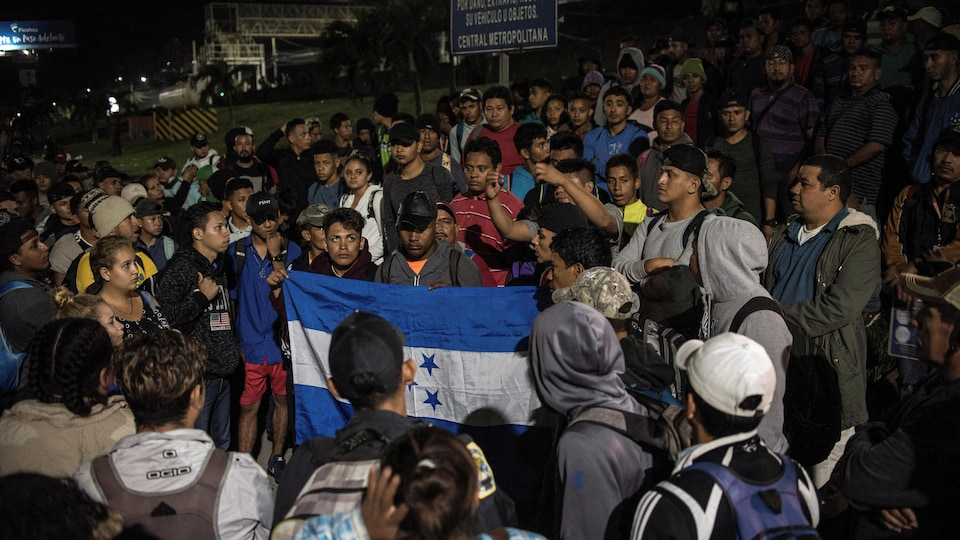 Des dizaines de personnes réunies. L'une d'elles tient un drapeau du Honduras.