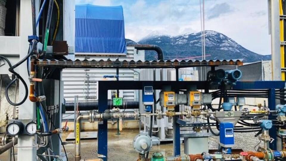 Une usine avec les montagnes de Squamish en arrière-plan