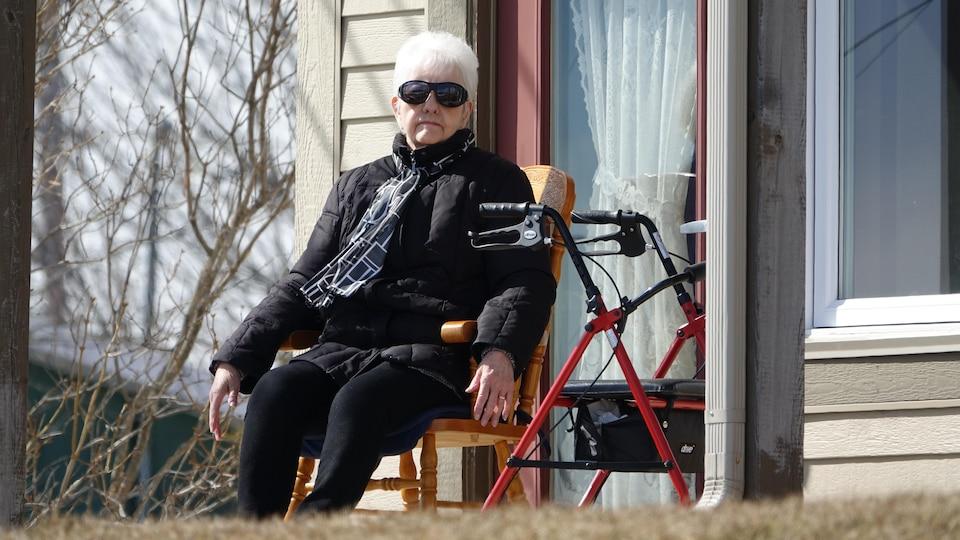 Une dame assise avec une marchette