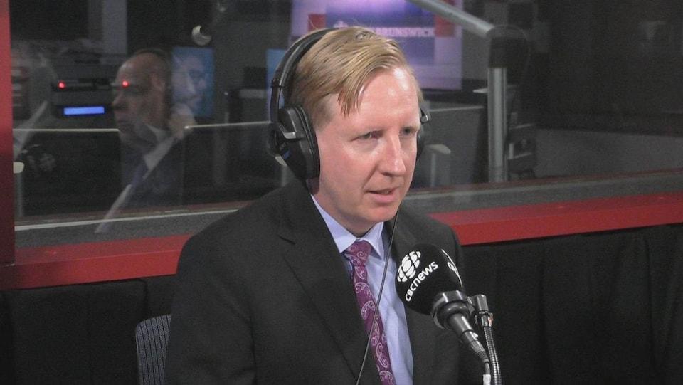 Dominic Cardy en entrevue dans un studio radiophonique