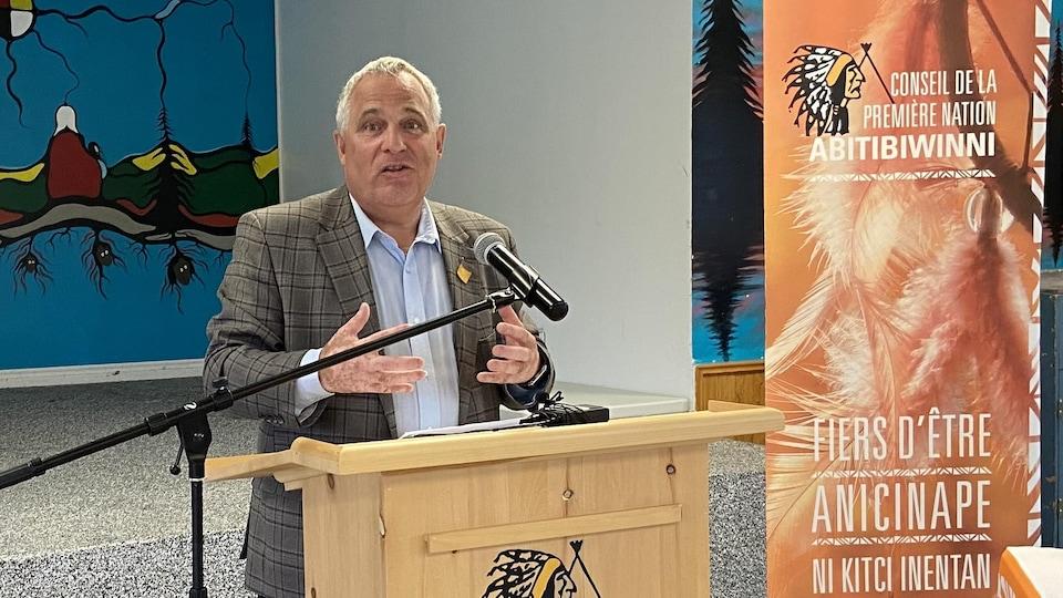 Marc Serré lors d'une conférence de presse près d'une oriflamme du Conseil de la Première Nation Abitibiwinni.