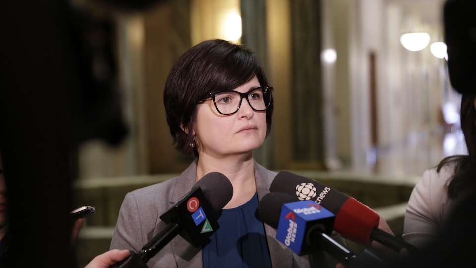 Carla Beck devant des micros en train de répondre aux questions des journalistes.
