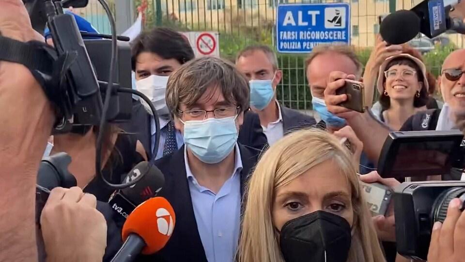 Carles Puigdemont au milieu d'un groupe de journalistes.