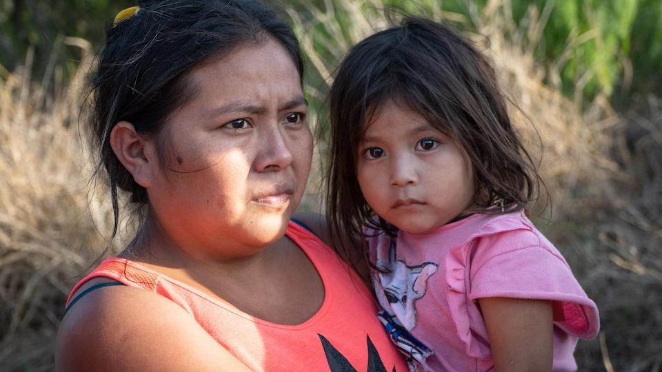 Une mère porte sa fille dans les bras.