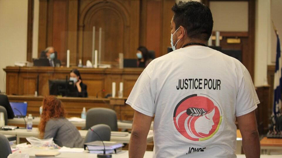 Un homme se tient debout lors d'audiences publiques dans un palais de Justice.