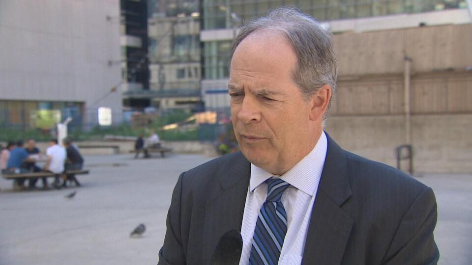 Carol Jolin, président de l'AFO dehors en entrevue avec Radio-Canada, il porte un veston noir, une chemise blanche et une cravate rayée bleue