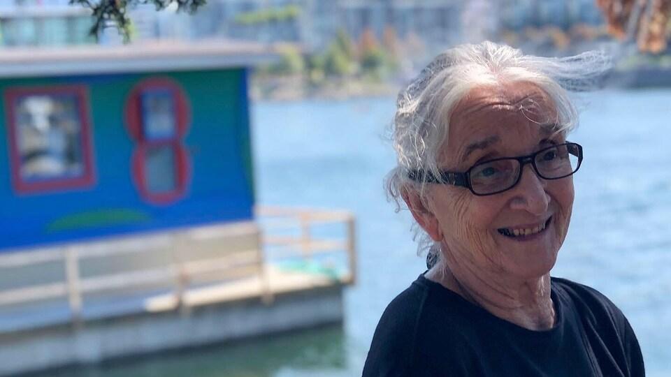 Une femme rit, en arrière-plan se trouve une cabine bleue sur l'eau.