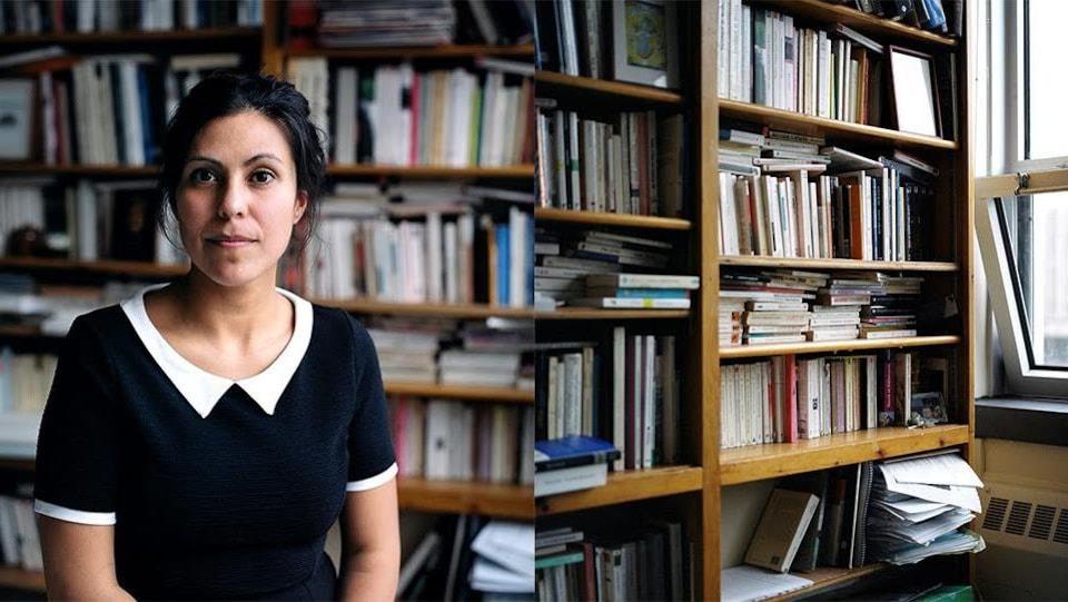 Portrait de l'autrice Caroline Dawson devant les rayonnages d'une bibliothèque.